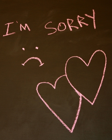 i am sorry: Im Sorry written on a blackboard with a sad face and intertwined hearts