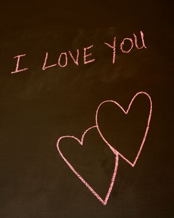 intertwined: I Love You written on a blackboard with intertwined hearts