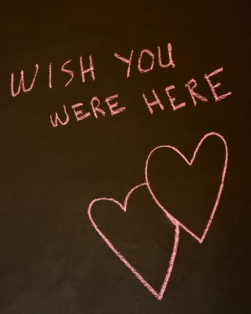 Wish You Were Here written on a blackboard with intertwined hearts