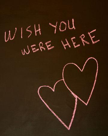 Wish You Were Here auf einer Tafel mit ineinander verflochtenen Herzen geschrieben  Standard-Bild - 5513254