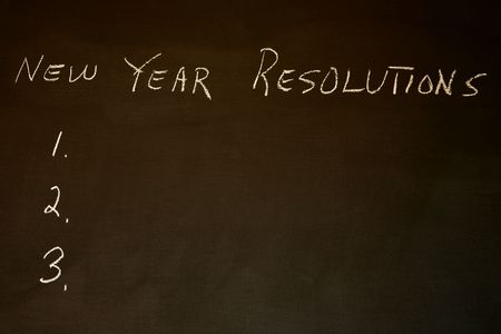 New Years Resolutions written on blackboard with copy space Stock Photo