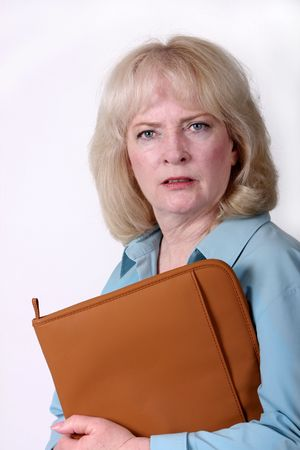 mean: Blond business woman in her 50s looks at the camera with an irritated expression