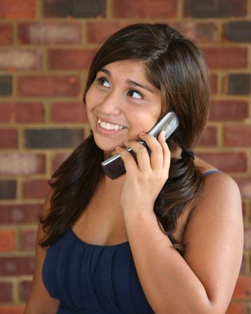 Cute, happy hispanic girl on the cell phone photo