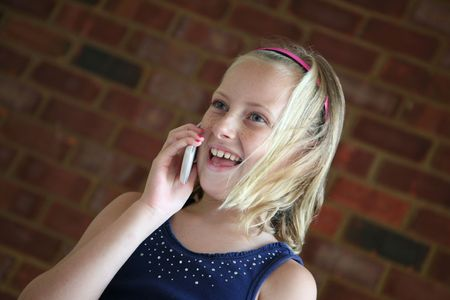 Young blond haired girl is laughing as she talks to a friend on her cell phone
