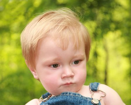 One year old boy wearing overalls stares at the ground Stock Photo - 5528318