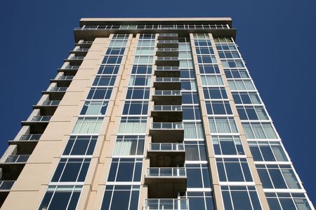 A nearly new condo sits mostly empty against a cobalt blue sky.