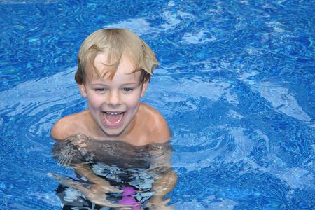 Young boy playing in swimming pool