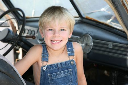 Young boy sitting in an antique car wearig old overalls Imagens