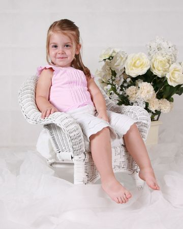Little girl in a wicker chair smiling photo