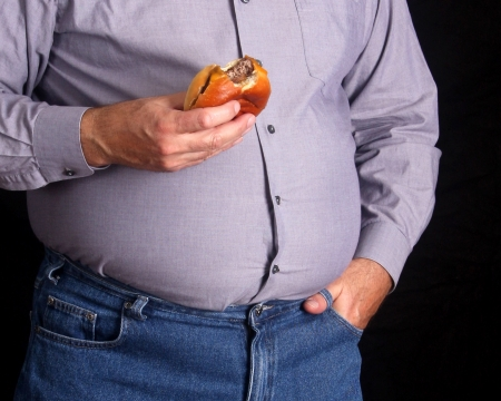 over eating: Overweight man eating a cheeseburger