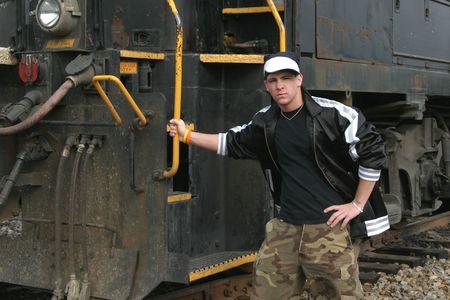 Teenage boy leaning against a railroad locomotive photo