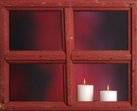 Christmas candles buring as seen through an old window photo