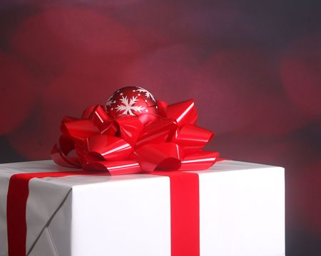elegantly: Elegantly wrapped Christmas present with red bow and snowflake ornament Stock Photo