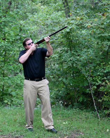 Man aiming a shotgun photo