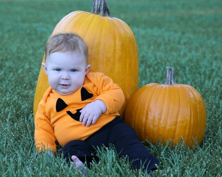 large pumpkin: Adorable 4 month old baby girl resting against a large pumpkin Stock Photo