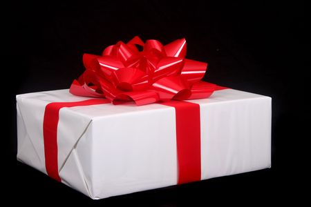 beautifully wrapped: Beautifully wrapped Christmas present set against a black background for dramatic effect