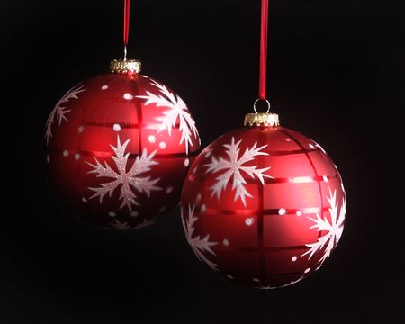 Snowflake Christmas ornaments set against a black background fr dramatic effect
