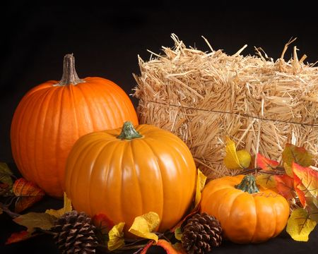 Pumpkins, colored leaves and a bale of hay make a perfect fall image. Stock Photo