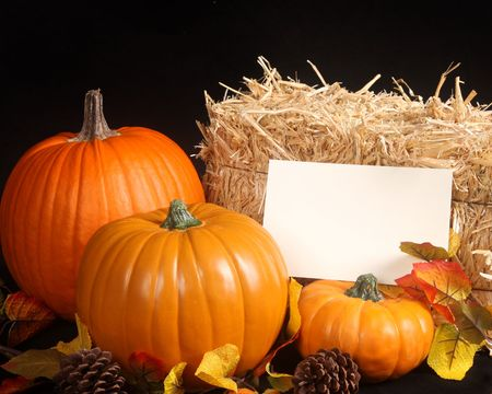 Pumpkins, colored leaves and a bale of hay with copy space for your holiday message photo