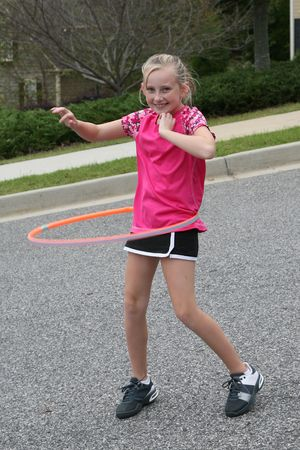Nine year old girl exercising with a hula hoop photo