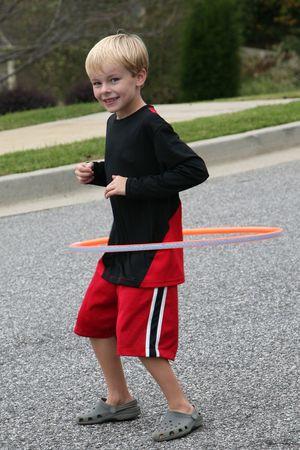 Sechs Jahre alten junge Ausübung mit einem Reifen (Spielzeug) Standard-Bild