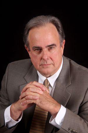 Reife Geschäftsmann mit einem schweren Ausdruck, die vor einem schwarzen Hintergrund festlegen