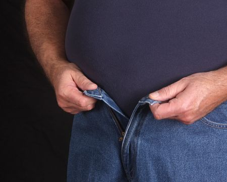 Overweight man trying to button his jeans Stock Photo