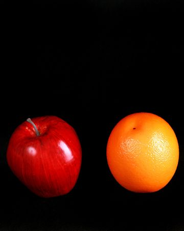 Apple and orange isolated on black with copy space