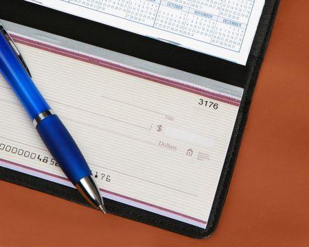 Scheckheft mit Stift auf Lederhintergrund