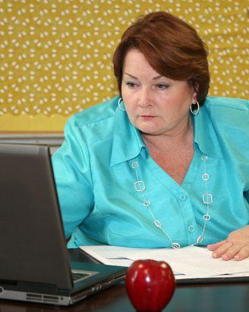 Older teacher staring at her computer Stock Photo