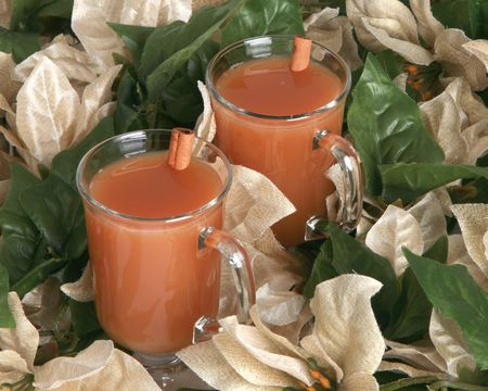 Hot apple cider with cinnamon sticks and holiday flowers photo