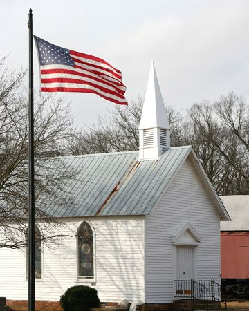church window: American flag in front of an old church Stock Photo