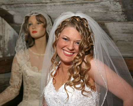 Young bride and a vintage mannequin in wedding dresses photo