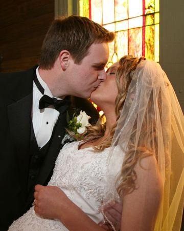 each: Bride and groom kissing at the altar