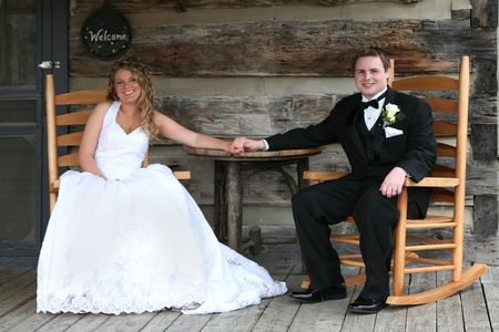Wedding couple sitting on a porch of a log cabin