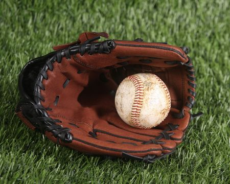 Baseball and glove laying in the grass photo