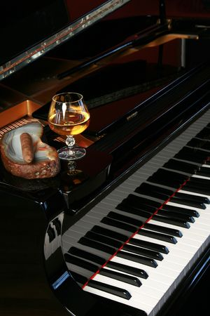 Piano with cigar and brandy or cognac snifter