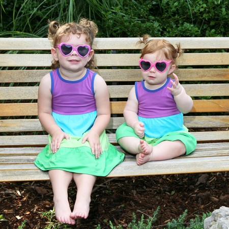 1 2 years: Two baby girls on a bench wearing sunglasses-2 Stock Photo