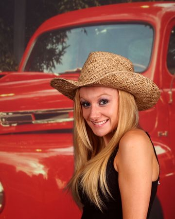 Country girl in front of an old pickup truck, no markings on truck
