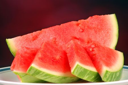 Watermelon slices set against a red background
