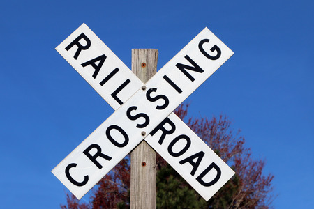 wood railroad: Railroad crossing sign against blue sky background Stock Photo