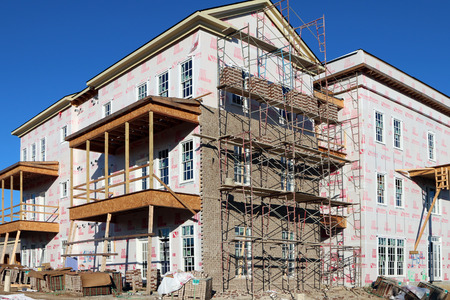 townhome: FRANKLIN, TN-SEPTEMBER, 2015:  Upscale condos under construction in a planned community.  The scaffolding for the brick layers is prominent in the image.