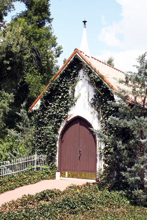 puertas de madera: Pequeña capilla o iglesia con puertas de madera en una zona boscosa, cubiertos de hiedra.
