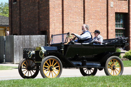 greenfield: DEARBORN, MI-MAY, 2015:  Couple driving in their Ford Model T historic automobile at Greenfield Village in Michigan.  Greenfoeld Village was started by Henry Ford.