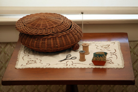 Old fashioned sewing basket and accessories sitting on a table, circa 1850s.