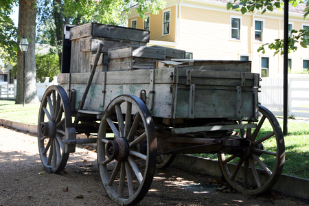 horse drawn: Horse drawn wagon sitting at rest on a city street.