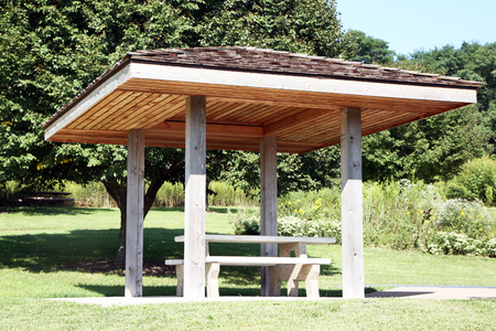 Roadside rest area with a picnic table and trees in background. There is a cover or canopy over the picnic table. Imagens