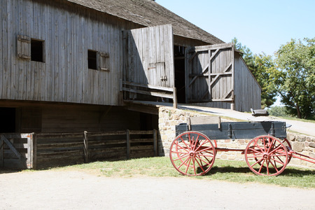 horse drawn: Horse drawn buggy setting in front of a large barn on the farm.