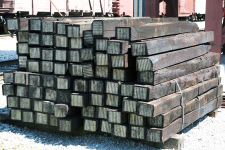 split level: Stack of new railroad ties sitting next to the railroad tracks. Stock Photo