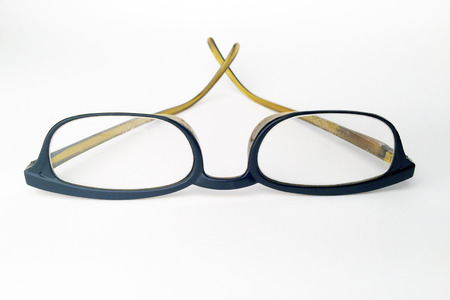 Pair of used reading glasses isolated on white.  The image is extremely close focused on the lens and the glass stems are slightly out of focus. Stock Photo